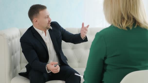 businessman sitting on couch talking to female psychologist