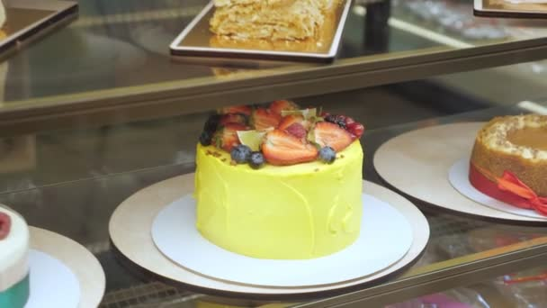 Yellow cake with fresh berries and cream in bakery showcase on glass shelf.