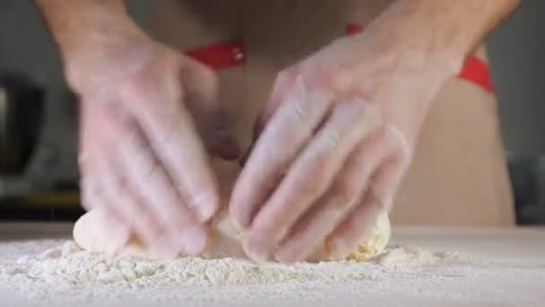 Küchenchef Bäcker knetet Teig mit Mehl auf dem Tisch.