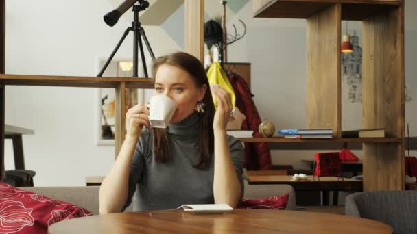 Young woman is meeting in the cafe for two friends drinking a cup of coffee.