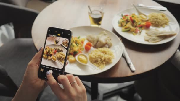 Woman blogger takes pictures of her food in a cafe using mobile phone.