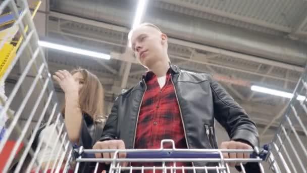 Mladí manželé kupují výrobky v supermarketu a staví je na vozík.