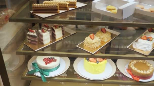 Pekařské vitrín s dortíky a pečivo na skleněných policích.