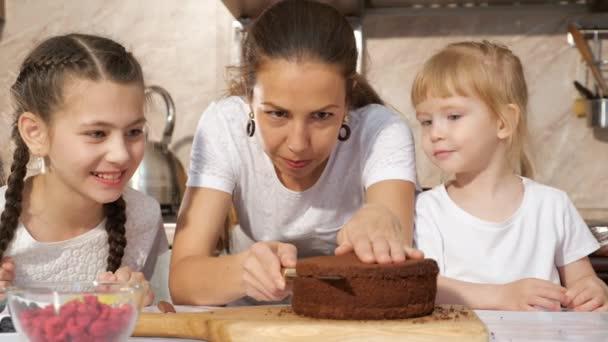 Šťastná rodinná máma a dcery spolu vaří narozeninový dort.