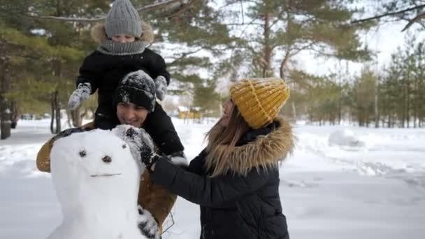 Mladá rodina, Máma, syn a otec staví v zimním městském parku sněsníka.