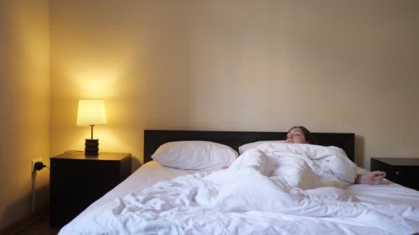 Nő felébred reggel, ülés és nyújtás az ágyban.