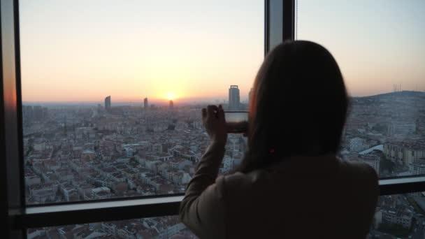Frau fotografiert Stadtpanorama bei Sonnenuntergang mit Smartphone in ihrer modernen Wohnung im Wolkenkratzer.