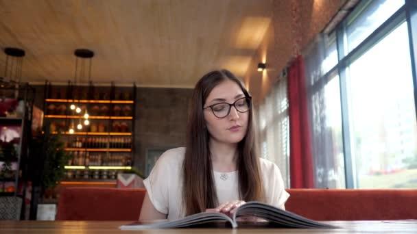 Hezká dívka, která čte menu a objednáve.