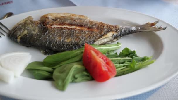 Mann gießt Fisch mit Zitronensaft auf den Teller mit grünen Blättern und Tomate.