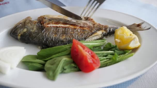 Man is eating frying fish with fork and knife in restaurant, dish closeup.
