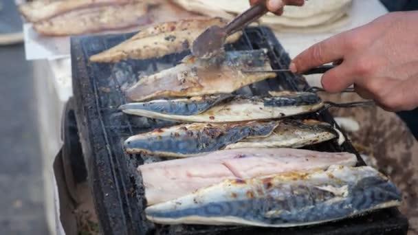 Člověk smaží bílou rybu Balyk na grilu na pouličním trhu, s rukama uzavíjením.