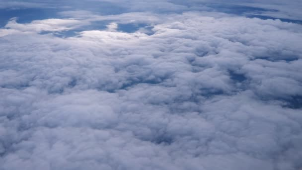 Letí nad vrstvou mraků a dívá se na krajinu skrz mraky.