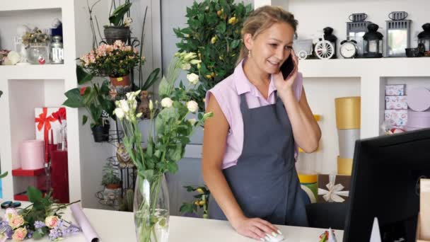 Woman florist seller in flower shop takes order on phone and workes on computer.