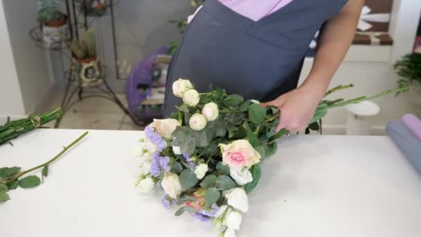 Woman florist makes bouquet from roses, gypsophila and leaves, closeup hands.