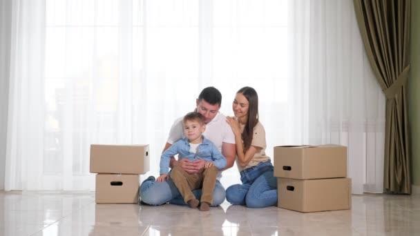 Netter Junge rennt durch neues Haus in der Nähe von Eltern, die auf dem Boden sitzen