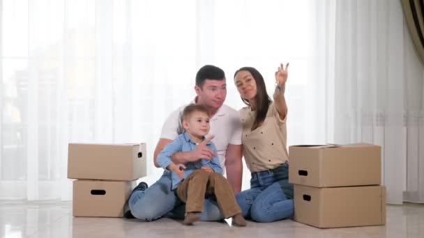 rodina se synem sedí na podlaze manželka ukazuje klíče k novému domu
