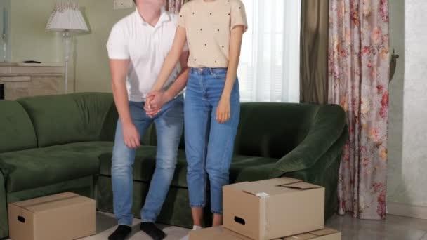 Paar in blauer Jeans legt Hand an und setzt sich auf grünes Sofa