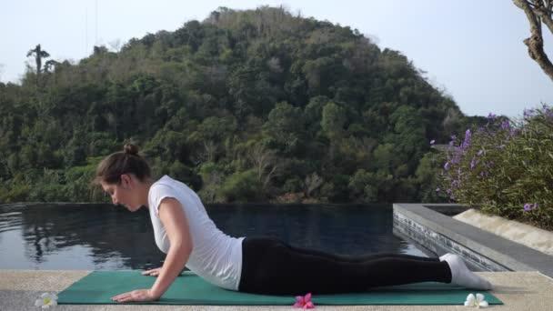 Junge Frau in Fitness-Uniform beim Stretching am Pool im Freien