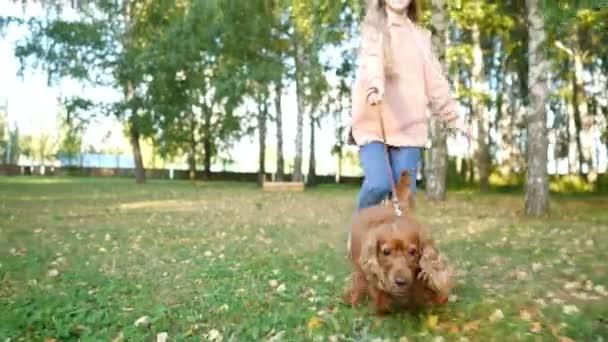 Mädchen läuft durch grünen Park mit lustigem Ingwerhund an der Leine