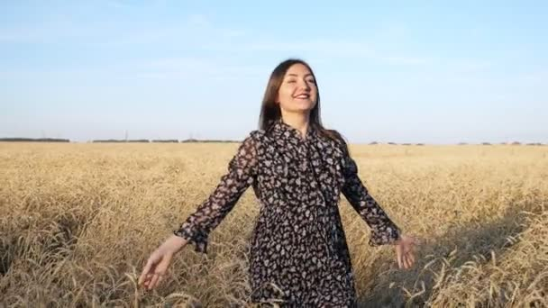 Young woman in dress walks and twirls smiling in a field of ripe wheat