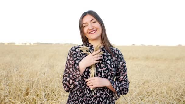 Mladá žena s kyticí zralých pšeničných uší na poli