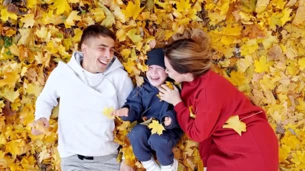 Šťastná rodinná hra ležící na zemi pokryté žlutými listy