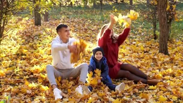 Szép család dob száraz sárga levelek napfényes őszi parkban