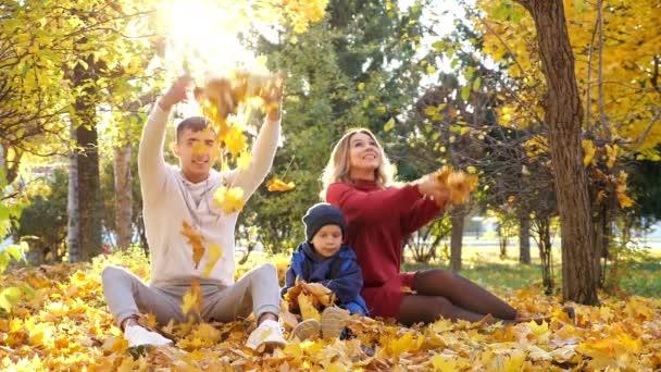 Krásná rodina háže suché žluté listy ve slunečném podzimním parku