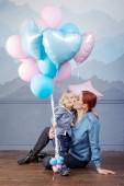 Anya és fia játszik a ballonok. Boldog család fogalmának. A gyerek születésnapja