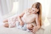 Fotografie Junge Mutter auf ihr neugeborenes Baby. Schöne Mutter mit einem niedlichen schlafenden neugeborenen Kind im Bett liegend. Babys erste Tage in Familie zu Hause.