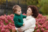 Quiet mother and her lovely little boy in a park. Cute child playing with mother in the park. Mother and son embracing.