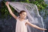 Fotografie schönes kleines Mädchen, das mit leichtem Stoff gegen die Blumen spielt