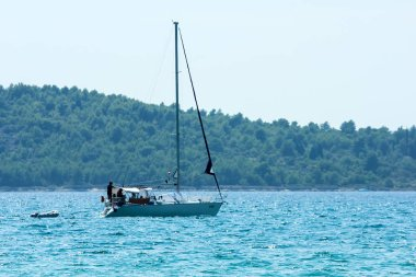 A picture of a boat floating on the blue ocean during the hot summer day. Relaxing vacation activity for the people.