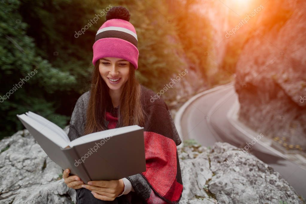 Hipster smiling girl is reading book in mountains.