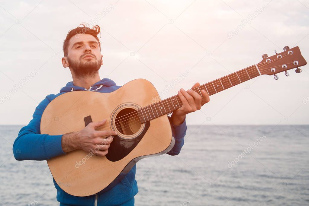 Portrait of hipster with guitar on sea background