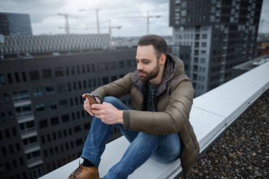 Smiling and bearded hipster guy looks at the social network in the smartphone, on the roof of a tall building