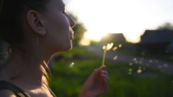 Nahaufnahme eines Teenagers, der Löwenzahn bei Sonnenuntergang bläst.