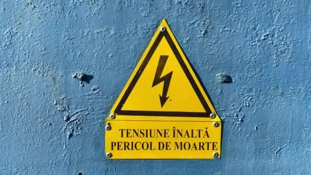 Nahaufnahme des gelben Hochspannungsschildes an der blauen Tür.