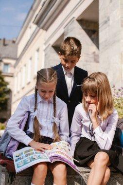 Schoolchildren have fun in the schoolyard.Children hurry to school.back to school