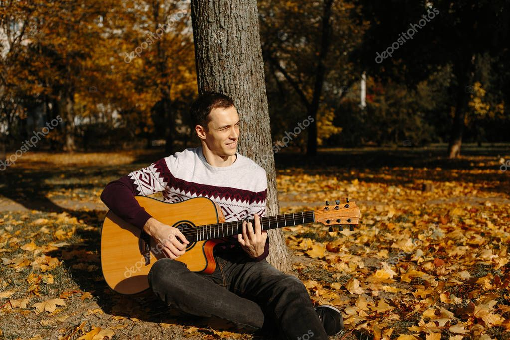 Handsome guy with guitar in the autumn park