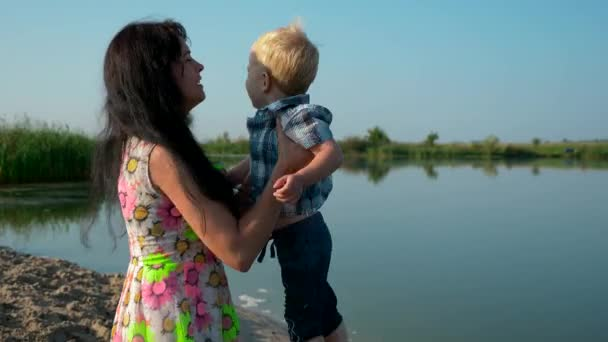 Happy Beautiful Mother Takes Child On Hands And Spinning Circling Turning Around. Joyful Positive Emotions Of Love. Summer River Lake Morning Sunny Day Blue Sky. Slow Motion 30p 0.5 60p