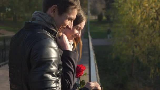 4 k 60p šťastný pár na mostě v městském parku. Romantické rande. Radostný muž a žena drží za ruce. Podzimní slunečný den