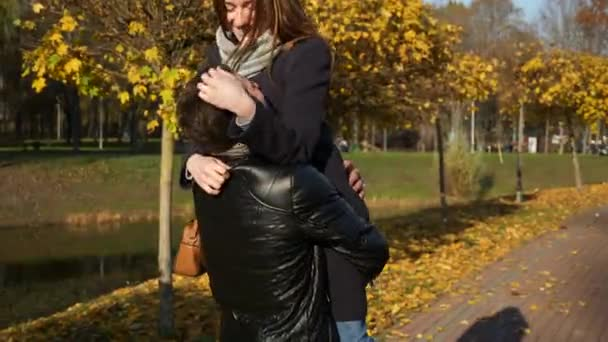 4K 60p Man Takes Girlfriend On Hands. Happy Couple Dating. Romantic Walk In City Park. Man And Woman Hugging. Autumn Sunny Day