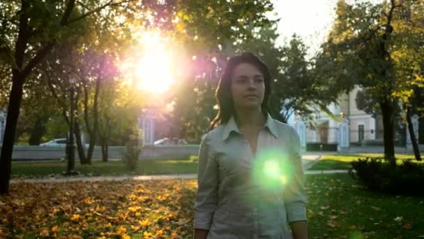 Confident Beautiful Successful Woman Walks In City Park And Thinking. Evening Sunset Background. Autumn Sunny Day In City Park. Lens Flare. Slow motion 4K 60 fps