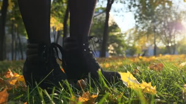 Close-up Female Footsteps Slow motion. Yellow Leaves On Green Grass Lawn In City Park. Bright Sunny Autumn Morning Evening