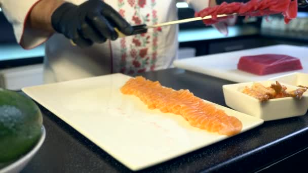 Close-up Hands With Kitchen Knife Cutting Salmon Red Fish Meat Slices. Chef Cook Preparing Japanese Traditional Sushi and Nigiri At Restaurant. Food Ingredients For Cooking Meal