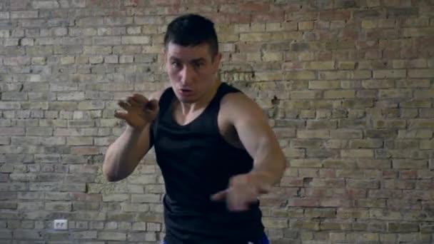 Tritte und Schläge in Zeitlupe in die Kamera. Muay Thai Boxer beim Training im Studio. Schattenkampf. Backsteinmauer