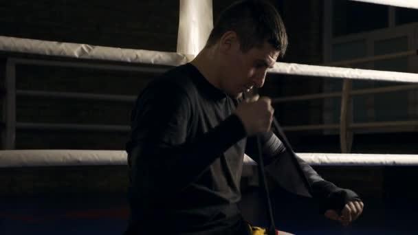 Muay Thai Boxer in Zeitlupe beim Anlegen von Handwickeln im Boxring