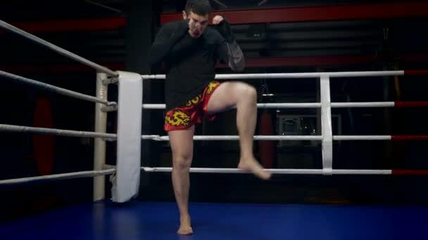 Muay Thai Kämpfer in Zeitlupe bläst mit dem Fuß schnelle, kräftige Schläge. Trainingskick im Boxring im Fitnessstudio