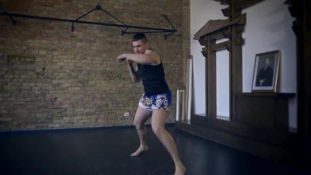 4k 60p Muay Thai Boxer Training im Studio. Schattenkampf. Backsteinmauer Hintergrund. Ostportal. Japanische Wörter auf der Malerei: Seele (oder Geist) des Kriegers (oder Samurai))